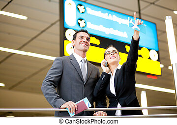 business travelers checking boarding information - two...