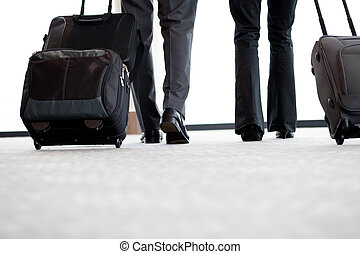 business travelers walking in airport with luggage