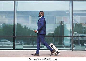 African businessman walking with luggage, arriving at airport.
