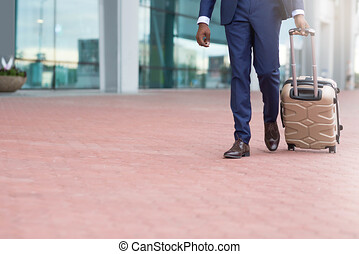 Business trip. Businessman walking with luggage, arriving at airport