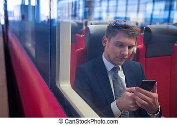 Business trip - Young businessman with a phone in a train