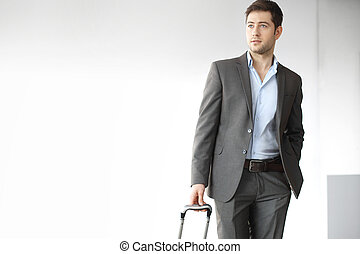 Business trip - A handsome man in a suit with a suitcase
