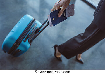 business trip - cropped shot of woman walking with suitcase...