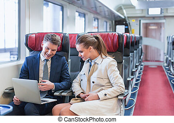 Business trip - Business people with laptop in a train