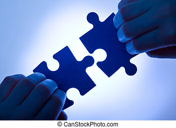 Business values - teamwork and collaboration concept with low key hands and puzzle pieces