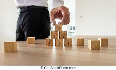 Business vision concept -businessman arranging wooden cubes