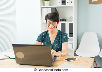 Business, web design and graphic art concept - Middle age woman working at the office with the smile on her face