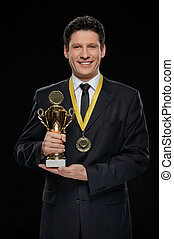 Business winner. Happy businessman holding a trophy while standing against black background