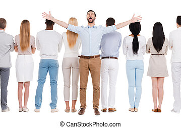 Business winner. Rear view of group of people standing in a row and against white background while one man standing face to camera and expressing positivity