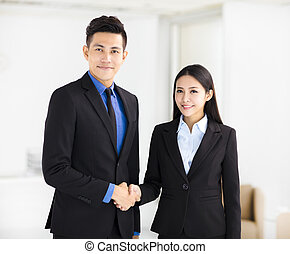business woman and man handshaking in office