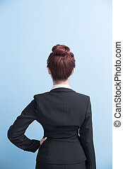 business woman arms akimbo and back to you with isolated on blue background, asian