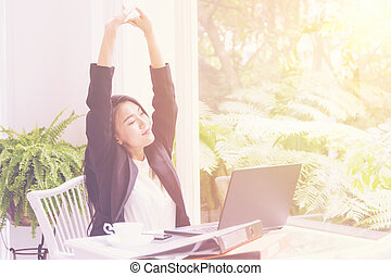 Business woman arms raised in office Relax and freedom concept after work hard