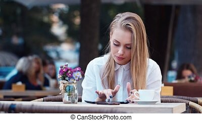 Business woman at a cafe working with the tablet