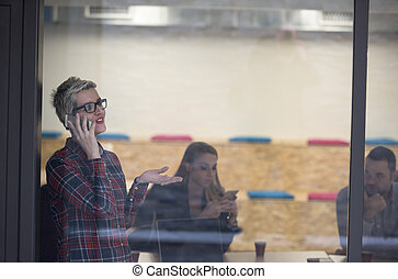 business woman at office speaking by phone  team on meeting in background