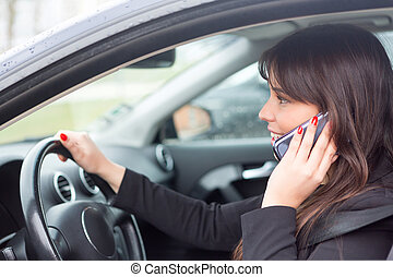 Business woman at the phone while driving