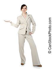 Beautiful young business woman in beige stripped suit over white. Standing with hand held out to side.