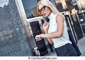 Business woman blond in glasses hurrying to a meeting