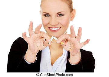 Business woman breaking a cigarette