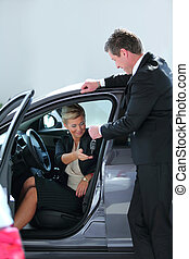 Business woman buying a car at dealership - Beautiful young...