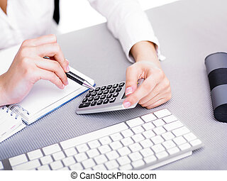 Business woman calculating with calculator