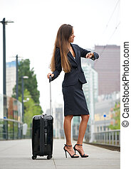 Business woman checking time at train station