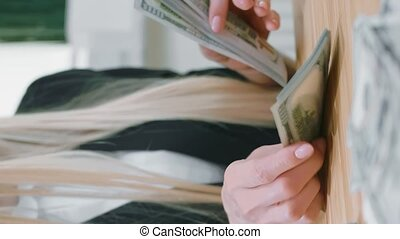 Crop view of female in elegant suit sitting at wooden desk and counting large bundle of dollar in hands. Video with Vertical Screen Orientation 9:16