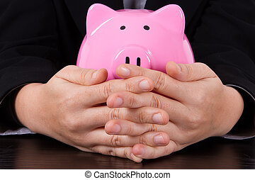 Business Woman Covering Piggy Bank
