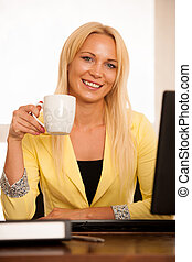 business woman drinks coffee in office