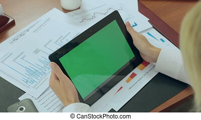 Business woman drives a finger on a tablet monitor with a green screen