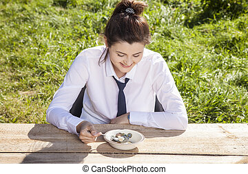 business woman eats breakfast in the open air, money in a plate