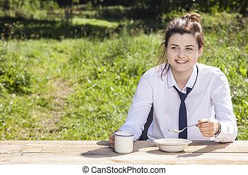 business woman eats breakfast in the open air