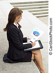 Business woman examines report document and writes in notebook
