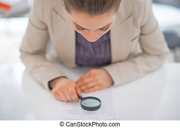 Business woman exploring document with magnifying lens