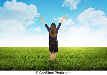 Business woman feeling happy on the meadow