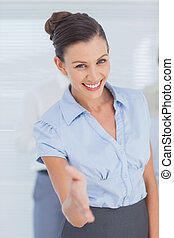 Business woman giving her hand for handshake in office