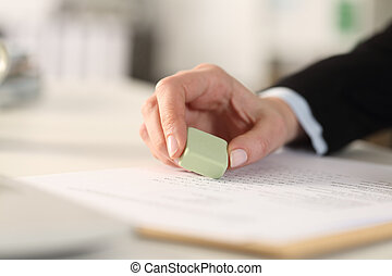 Business woman hand erasing form with rubber at the office