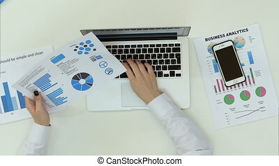 Business woman hand typing on laptop with financial charts on the table