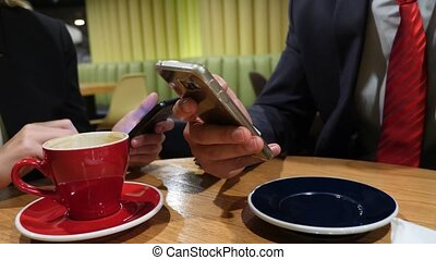 Business Woman ? ?????????? hands texting, sending sms on smartphone and drinking coffee in cafe. 4k.