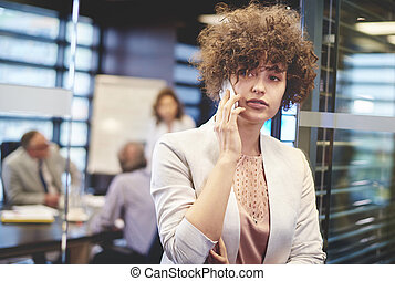 Business woman having a phone call at work