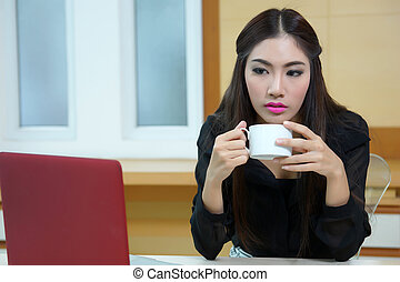 Business woman hold cup of coffee sitting at desk