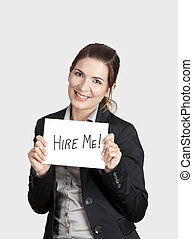 """Business woman holding a card board with the text message """"Hire me""""."""