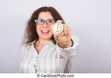 Business woman holding a Golden Bitcoin. Virtual money.