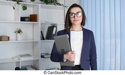 business woman holding a laptop looking at the camera