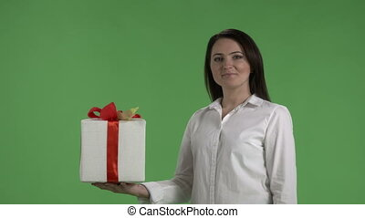 Business woman holding and showing red white gift box against green screen