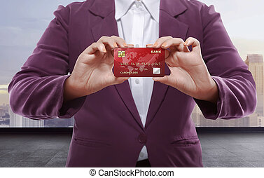 Business woman holding credit card against cityscape...