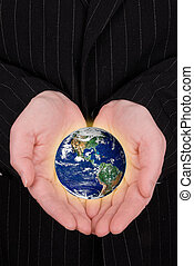 Business woman holding earth in her hands