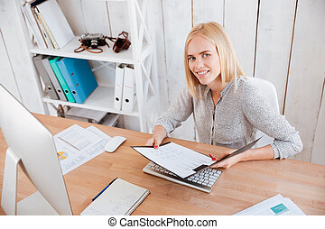 Business woman holding opened folder and looking at camera