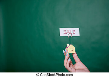 business woman holding small house .Hands presenting a small model of a house isolated on green background for sale. Little House on the hands, symbol of a successful real estate business. estate sale, property sale concept. Copy space
