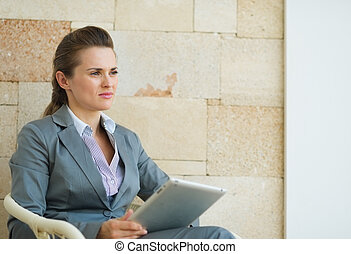 Business woman holding tablet PC and looking on copy space