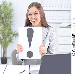 business woman holding the exclamation mark ,sitting behind a Desk